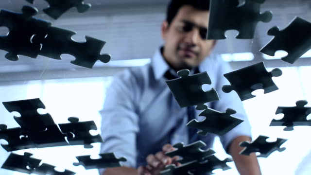 Businessman joining jigsaw puzzle on table, Delhi, India