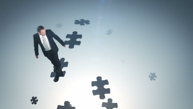 Businessman jumping on puzzle pieces