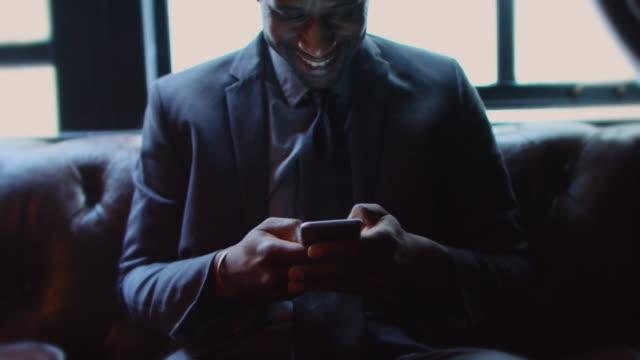 businessman laughing at phone - entusiasta di tecnologia video stock e b–roll