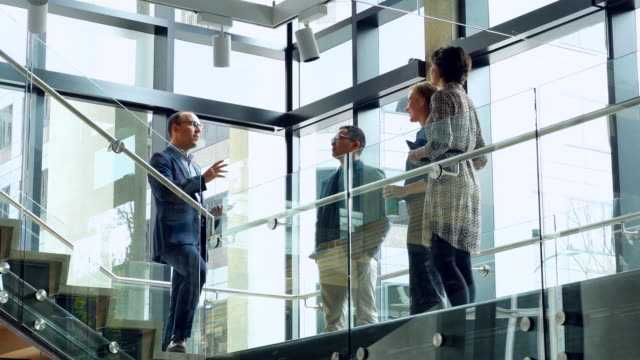 MS Businessman leading informal team meeting on office stairs