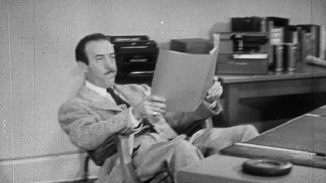 vídeos de stock, filmes e b-roll de b/w 1944 businessman leaning back in chair + falling over in office - divertimento