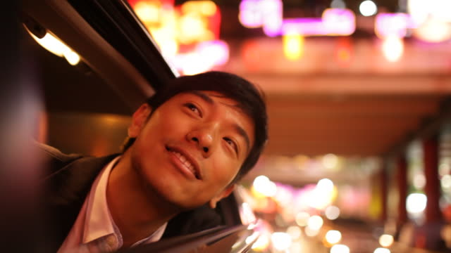 A businessman leans out of a car window while city lights reflect around his car.