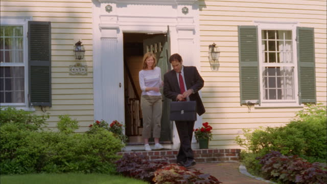 A businessman leaves a suburban home, picks up a newspaper, and waves goodbye to his wife.