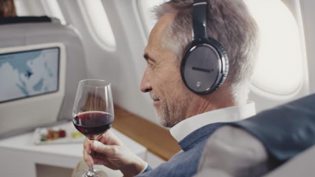 vídeos de stock, filmes e b-roll de empresário ouvindo música em jato corporativo - primeira classe