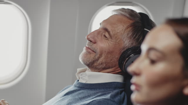 vídeos de stock e filmes b-roll de businessman listening music with headphones in jet - estrada da vida