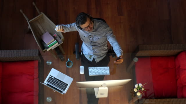 vidéos et rushes de homme d'affaires écoutant la musique avec des écouteurs dans le bureau - bien être