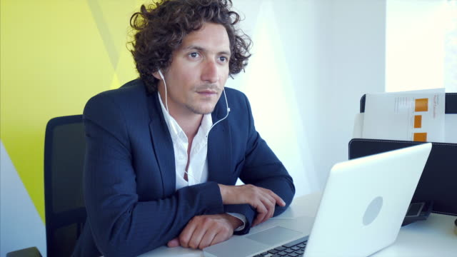 Businessman listening to laptop.