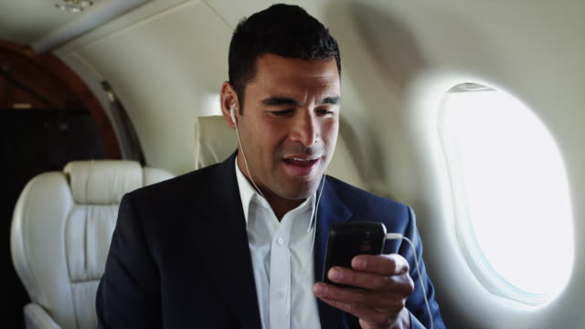 MS Businessman listening to MP3Player in airplane / Spanish Fork, Utah, USA