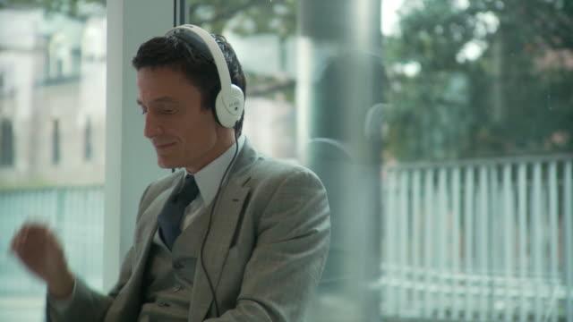 MS Businessman listening to music on headphones / South Orange, New Jersey, USA