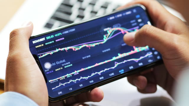 vídeos de stock e filmes b-roll de businessman look stock information on smart phone - investimento