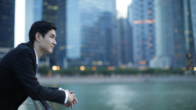 Businessman looking at buildings across the water.