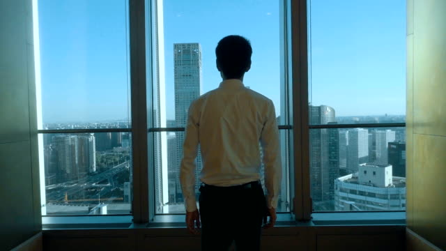Businessman looking at cityscape from office window