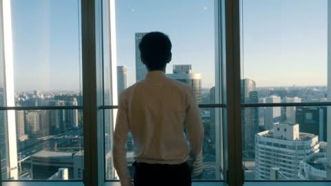 stockvideo's en b-roll-footage met zakenman kijken naar stadsgezicht van loket - window