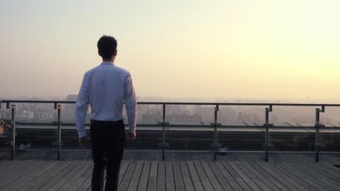 vídeos y material grabado en eventos de stock de businessman looking at cityscape - tejado