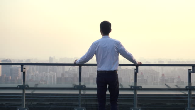 businessman looking at cityscape,standing on roof - 屋根点の映像素材/bロール