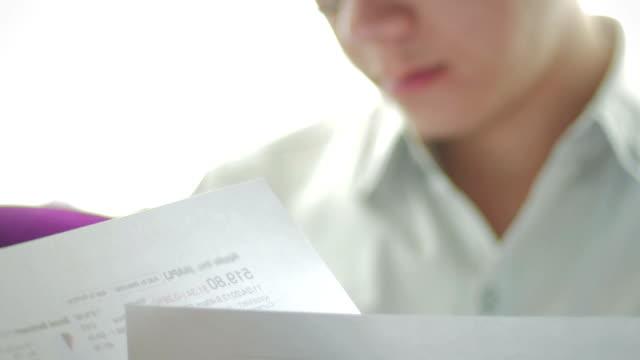 stockvideo's en b-roll-footage met businessman looking at financial documents,tilt up - financiële pagina