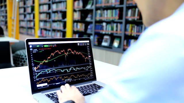 Businessman looking at graph stock Data on Laptop