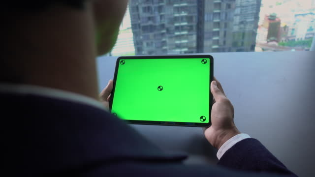 businessman looking at laptop with green screen - computer key stock videos and b-roll footage