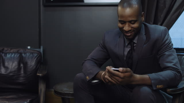 Businessman Looking at Phone in Lobby
