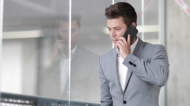 Businessman looking at reflection and using smartphone in an office
