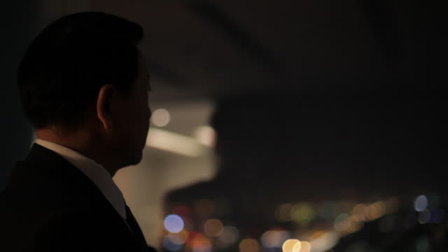 cu businessman looking at view of city at night / beijing, china - silhouette stock videos & royalty-free footage