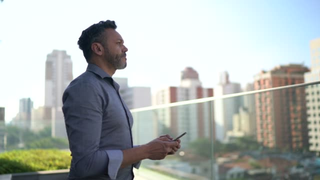 businessman looking away using mobile and contemplating at office rooftop - 50 54 years stock videos & royalty-free footage