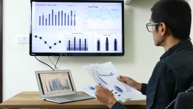 stockvideo's en b-roll-footage met zakenman op zoek naar business project en analyseren van markt data, dolly shot - testuitslag