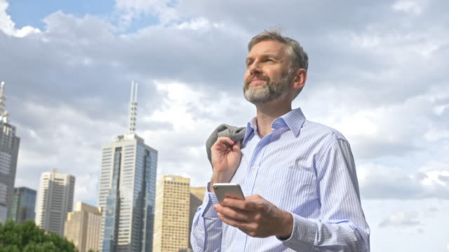 Businessman looking for directions in the city on mobile phone