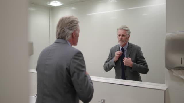 vídeos y material grabado en eventos de stock de businessman looking in a mirror preparing for business meeting - corbata