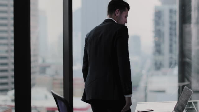 Businessman looking out at city skyline thinking