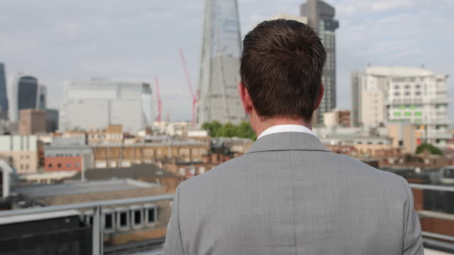 vidéos et rushes de businessman looking out at london city skyline - toit