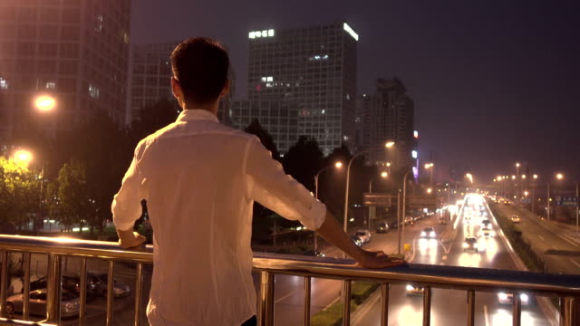 businessman looking out city at night - junger mann allein stock-videos und b-roll-filmmaterial