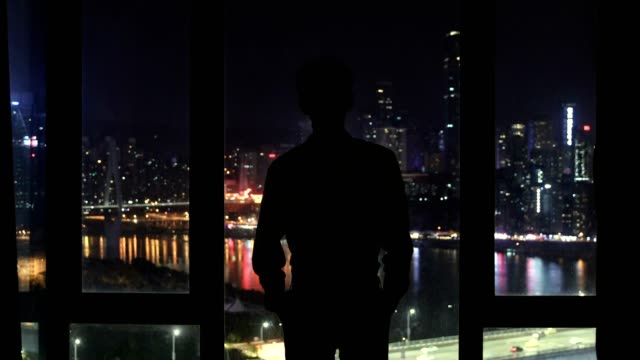 businessman looking out of window at night - looking through window stock videos & royalty-free footage