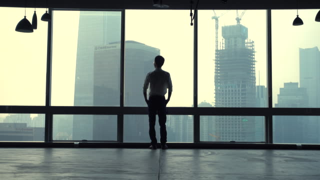 businessman looking out the window at city - 景色を眺める点の映像素材/bロール