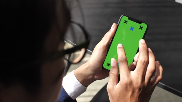 Businessman looking Smart phone green screen