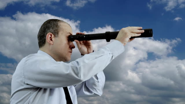 Businessman Looking Through a Hand-Held Telescope with Moving Clouds