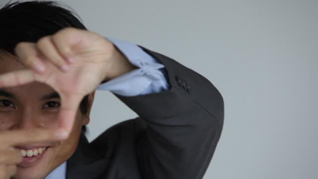 c/u businessman looking through finger frames - 25 29 years stock videos & royalty-free footage