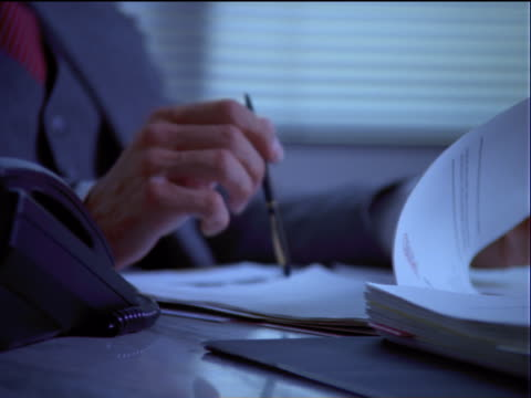 vídeos y material grabado en eventos de stock de businessman looking through papers - un solo hombre de mediana edad