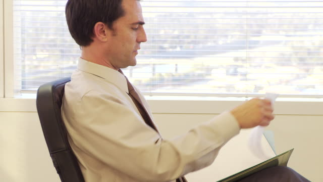 Businessman looking through paperwork files