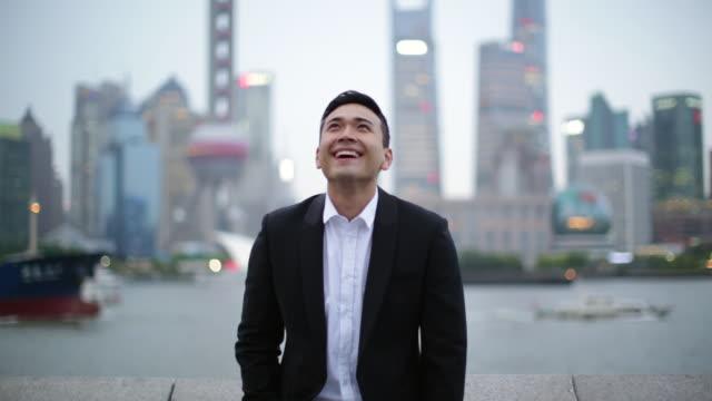 vidéos et rushes de ms businessman looking up and smiling, shanghai, china - en l'air
