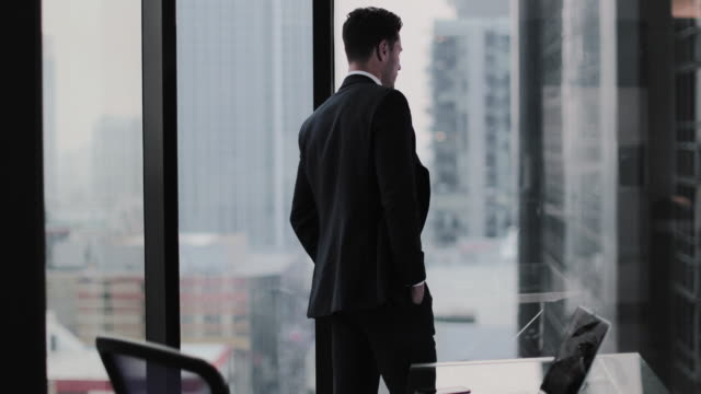 Businessman looking up at skyscraper thinking