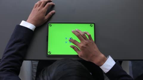 stockvideo's en b-roll-footage met zakenman op zoek naar digitale tablet groen scherm - over shoulder