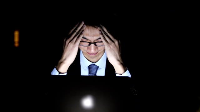 Businessman looking worried in office at night