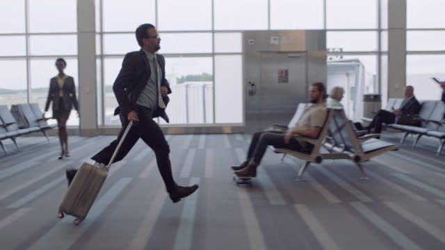 Businessman looks around as he runs through crowded airport waiting area.