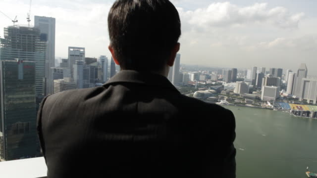 a businessman looks out over the city of singapore. - 25 29 years stock videos & royalty-free footage