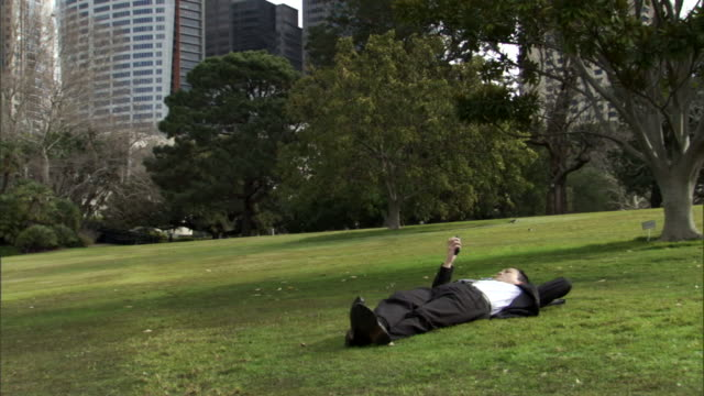 MS, Businessman lying on lawn in park and using mobile phone, office buildings in background, Sydney, Australia