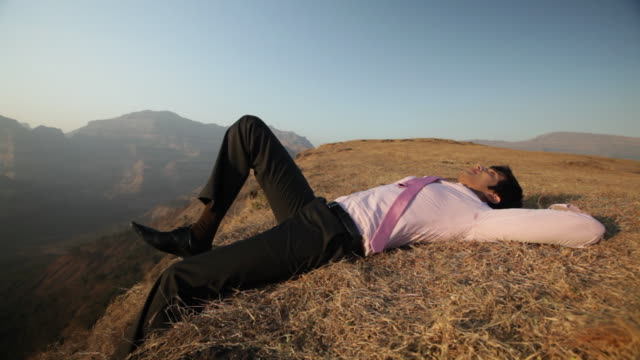 vídeos de stock, filmes e b-roll de businessman lying on the cliff of mountain  - camisa e gravata