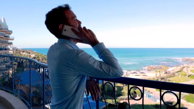 vídeos de stock, filmes e b-roll de empresário faz uma chamada no telefone de férias-vídeo stock - israel