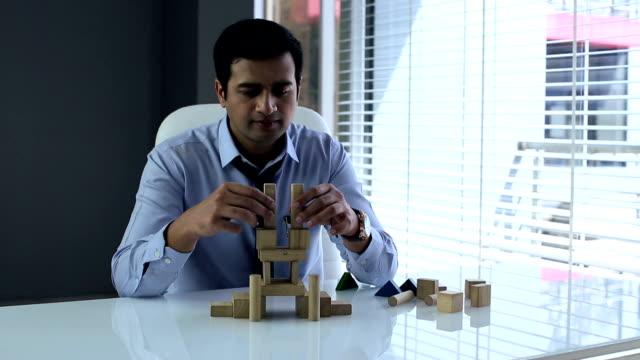 vídeos de stock e filmes b-roll de businessman making building blocks, delhi, india - camisa e gravata