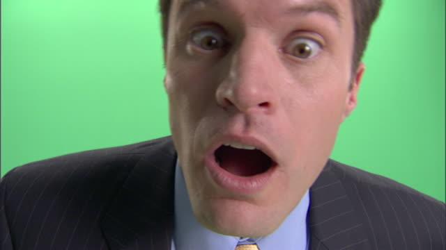 ecu, businessman making face into camera in studio - 盗み聞き点の映像素材/bロール